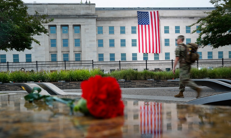 Photo Caption: A member of the military walks the grounds of the National 9/11 Pentagon Memorial before the start of the September 11th Pentagon Memorial Observance at the Pentagon on the 17th anniversary of the September 11th attacks, Tuesday, Sept. 11, 2018. (AP Photo/Pablo Martinez Monsivais)